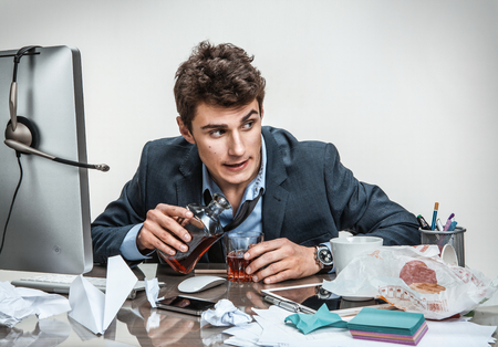 Drunk businessman sitting drunk at office with computer holding glass looking depressed wearing loose tie in alcohol addiction problem concept