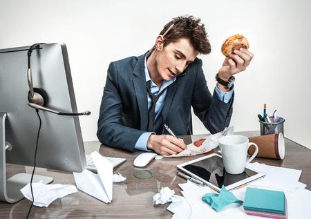 confundido: Joven hombre de negocios hablando por teléfono y escribiendo en su lugar de trabajo