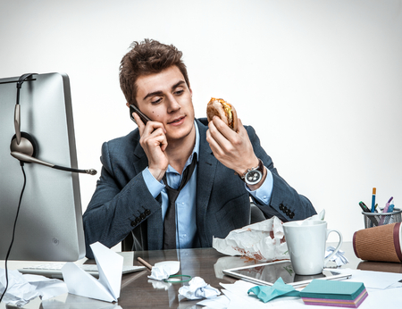 twiddle: Slacker man talking on the phone while eating at work  modern office man at working place sloth and laziness concept