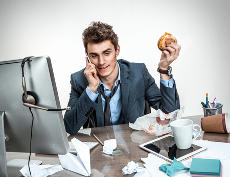 back in an hour: Modern office man calling during his breakfast at working place