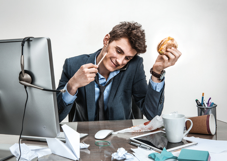 twiddle: Young business man talking on the phone while holding burger in one hand and pencil in the other looking down smiling  modern office man at working place sloth and laziness concept