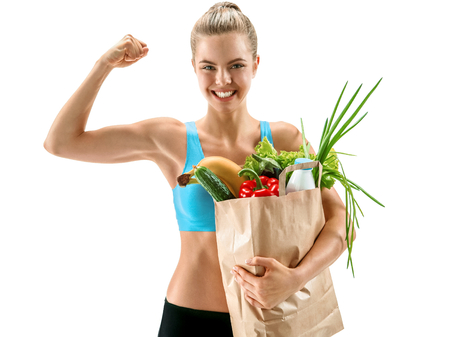 veggies: Happy cute athletic woman showing biceps with grocery bag full of healthy fruits and vegetables  photo set of cheerful brunette girl with healthy dietary eco organic food over white background Stock Photo