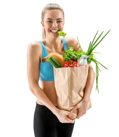 buena salud: Mujer sonriente linda con las frutas y hortalizas frescas en bolsa de papel ecológica salud alimentos y cuidado de la belleza concepto photo conjunto de niña morena alegre con comida ecológica orgánica dieta saludable sobre fondo blanco Foto de archivo