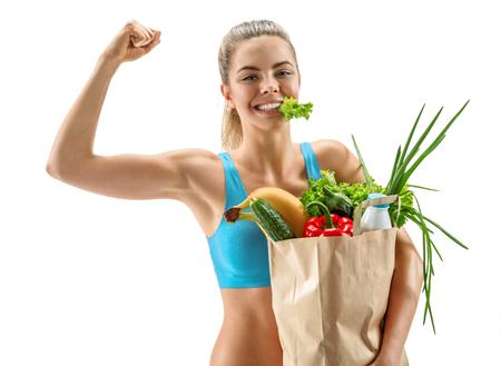 buena salud: Cutie mujer atlética feliz que muestra el bíceps con bolsa de supermercado llena de frutas y verduras saludables conjunto de fotos de la muchacha alegre morena con comida ecológica orgánica dieta saludable sobre fondo blanco
