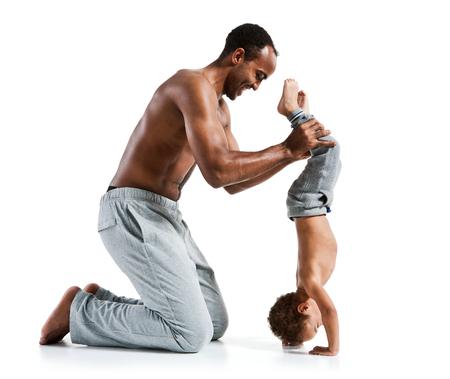 白い背景にスポーティな筋肉ヒスパニック上半身裸のフィットネスの男彼の息子の写真セットを逆さまに立っている幸せな子供