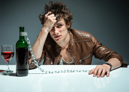 addiction drinking: Young drunk man with a bottle of red wine  photo of youth addicted to alcohol, alcoholism concept, social problem Stock Photo