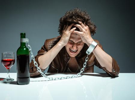 tomando alcohol: Hombre esposado interconectados con una botella de alcohol foto de la juventud adicta al alcohol, el concepto de alcoholismo, problema social Foto de archivo