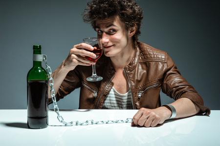 dipsomania: Man proposing a toast with a glass of red wine and looking at the camera   photo of youth addicted to alcohol, alcoholism concept, social problem