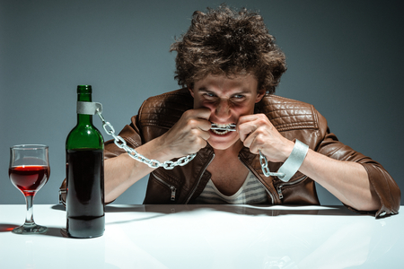 gyve: Young man is trying to gnaw the chains  photo of youth addicted to alcohol, alcoholism concept, social problem Stock Photo