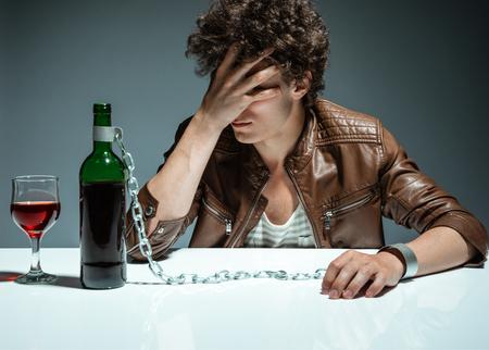 alcoholismo: Hombre triste y deprimida joven con fotografía adicción al alcohol de los jóvenes adictos al alcohol, el concepto de alcoholismo, problema social