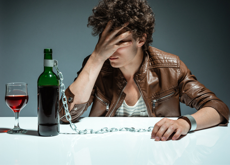 dipsomania: Sad and depressed young man in alcohol addiction  photo of youth addicted to alcohol, alcoholism concept, social problem Stock Photo