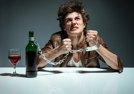 dipsomania: Young man is trying to break the chains  photo of youth addicted to alcohol, alcoholism concept, social problem Stock Photo