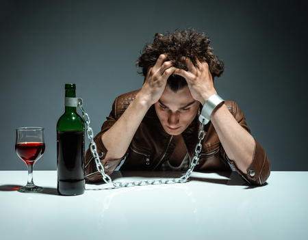the problem: Intoxicated man sitting alone  photo of youth addicted to alcohol, alcoholism concept, social problem