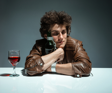 gyve: Young man is hugging a bottle of wine  photo of youth addicted to alcohol, alcoholism concept, social problem Stock Photo