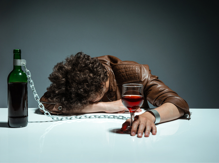 gyve: Young man passed out from alcohol  photo of youth addicted to alcohol, alcoholism concept, social problem
