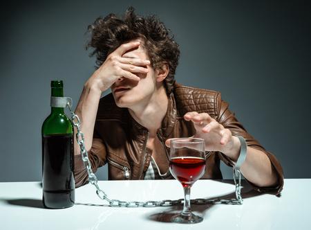 tomando alcohol: Hombre joven que bebe vino tinto y sintiendo foto desesperación de los jóvenes adictos al alcohol, el concepto de alcoholismo, problema social Foto de archivo