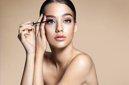 glamour nude: Woman applying black mascara on eyelashes with makeup brush  photos of appealing brunette girl on beige background Stock Photo