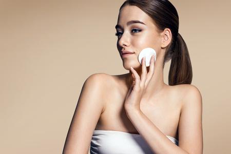 pulizia viso: Cura della pelle donna di rimuovere il trucco viso - la cura della pelle concetto foto di appello ragazza bruna su sfondo beige