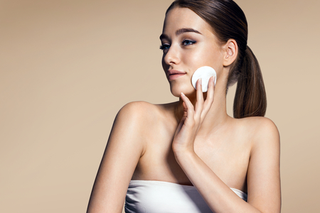 foundations: Skin care woman removing face makeup - skin care concept  photos of appealing brunette girl on beige background
