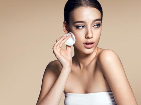 pulizia viso: Giovane donna che applica fondamento sul fronte con il soffio di cipria, il concetto di cura della pelle foto di attraente ragazza bruna su sfondo beige Archivio Fotografico