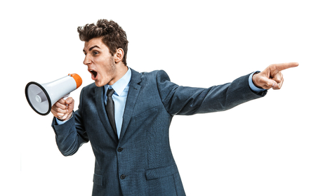 emphatic: Active manager shouting into a megaphone and finger pointing  photos of young businessman wearing  a suit and tie over white background Stock Photo