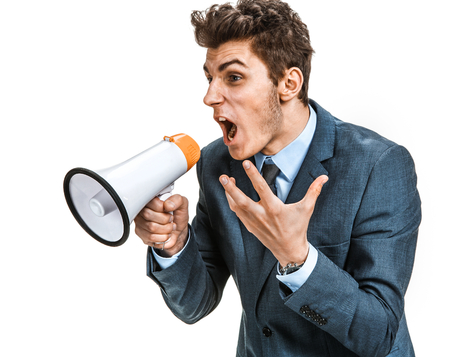 emphatic: Stressed man yelling through a megaphone   photos of young businessman wearing  a suit and tie over white background Stock Photo