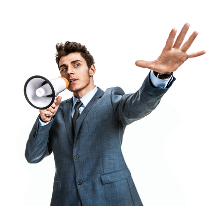 Young man shouting through a megaphone   photos of young businessman wearing  a suit and tie over white background