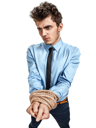 Mans hands tied together with rope, modern slavery concept  photos of young man wearing shirt and tie over white background