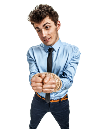 office slave: Handsome businessmans hands tied together with rope, modern slavery concept  photos of young man wearing shirt and tie over white background Stock Photo