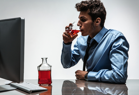 drunkenness: Young drunk caucasian businessman with bottle of alcohol  photo of businessman addicted to alcohol at the workplace, depression and crisis concept
