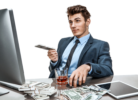 dipsomania: Young manager sitting at desk in office and thinking about his investment plan  photo of businessman addicted to alcohol at the workplace, mortgage and investment concept Stock Photo