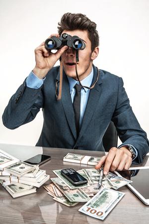 slacker: Young businessman looking through binoculars  photos of modern businessman at the workplace