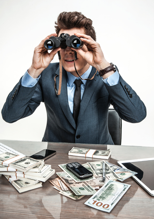 slacker: Guy spying with binoculars  photos of modern businessman at the workplace Stock Photo