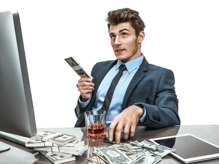 dipsomania: Young man sitting at desk in office and planning how to invest money for profit  photo of businessman addicted to alcohol at the workplace, mortgage and investment concept
