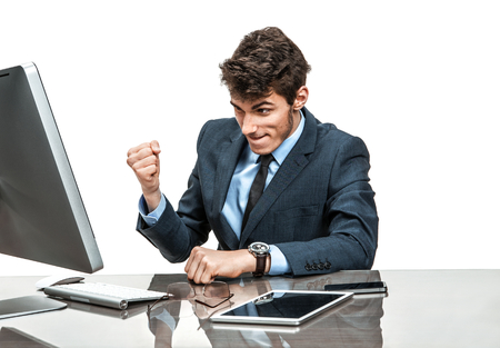 achiever: Cheerful manager is satisfied with his profit, income, earnings, gain, benefit, margin  modern businessman at the workplace working with computer Stock Photo
