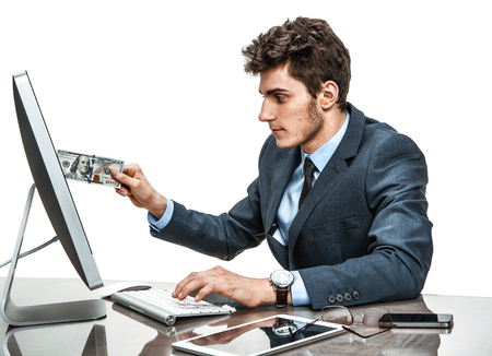 money online: Businessman inserts money into a monitor, paying online concept  modern businessman at the workplace working with computer