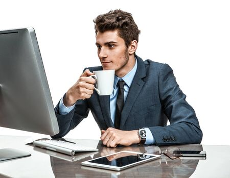 coffeebreak: Handsome businessman having a coffee-break in office sitting at the table  photos of modern businessman at the workplace