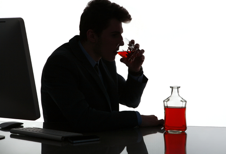 drinking alcohol: Silhouette of alcoholic drunk man drinking whiskey   photo of businessman addicted to alcohol at the workplace, depression and crisis concept