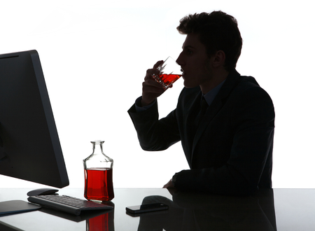 dipsomania: Silhouette of alcoholic drunk young man drinking rum  photo of businessman addicted to alcohol at the workplace, depression and crisis concept Stock Photo