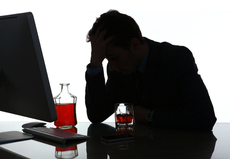 Silhouette of alcoholic drunk young man  photo of businessman addicted to alcohol at the workplace, depression and crisis concept Foto de archivo