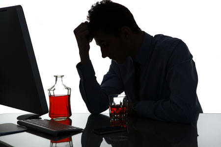 addiction drinking: Silhouette of sad and depressed young man in alcohol addiction  photo of businessman addicted to alcohol at the workplace, depression and crisis concept