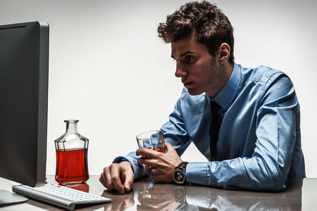 inebriated: Drunk man sitting drunk at office holding glass   photo of businessman addicted to alcohol at the workplace, depression and crisis concept