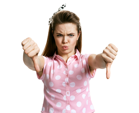 pissed off: Unhappy angry mad pissed off woman, annoyed wife, giving thumbs down gesture looking with negative facial expression and disapproval photo of young brunette woman over white background, negative emotions