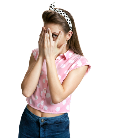 hands covering face: Surprised girl peeking through hands covering face photo of young cheerful brunette woman over white background, positive emotions