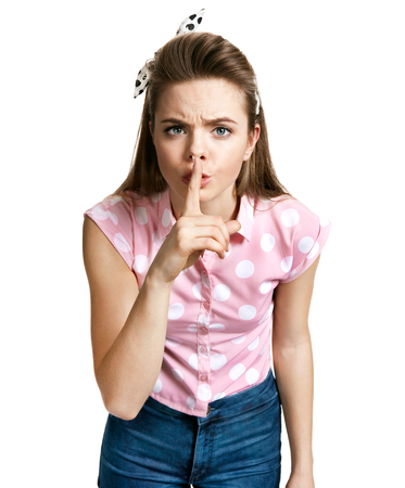 shh: Girl holding her finger to her lips in a gesture for silence, keep it quiet gesture - shh