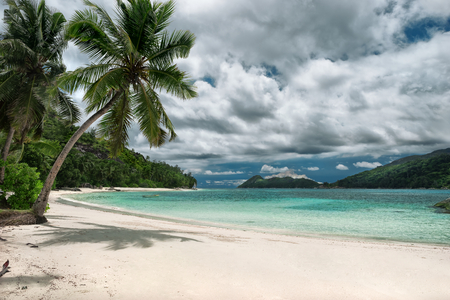 nature wallpaper: Untouched tropical beach, cloudy sky outdoors photography of picturesque Seychelle islands Stock Photo