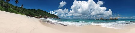 beach panorama: Tropical sandy beach with clouds and blue sky at summer sunny day, panorama outdoors photography of picturesque Seychelle islands