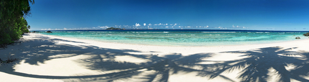 beach panorama: Beautiful tropical sandy beach with shadows of the coconut palm trees. Panorama outdoors photography of picturesque Seychelle islands