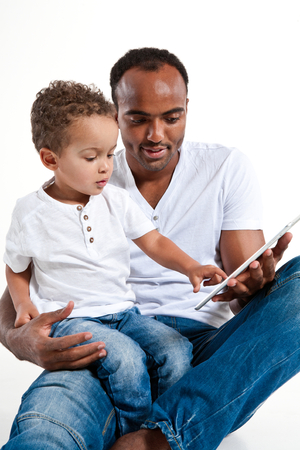 Father and son looking at tablet PC
