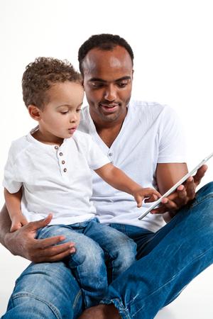 Vader en zoon die tabletpc bekijken Stockfoto